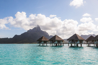 Stilt houses in lagoon of Bora Bora island by mountain against cloudy sky - CAVF13350