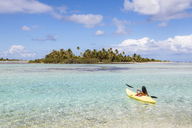Woman kayaking in lagoon against sky - CAVF13362