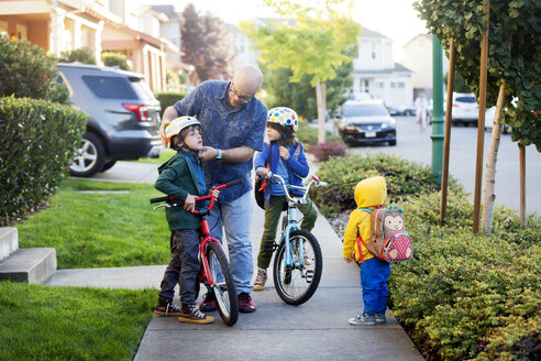 Father preparing sons for cycling while standing outside house - CAVF13500