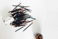Overhead view of scattered colored pencils on table - CAVF13527