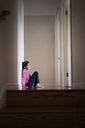 Side view of girl sitting on floor by wall at home - CAVF13554
