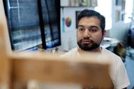 Painter looking at easel in art studio - CAVF13629