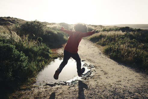 Rear view of boy with arms outstretched jumping over puddle on dirt road against clear sky - CAVF13656