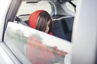 Boy reading book in car seen through window - CAVF13659