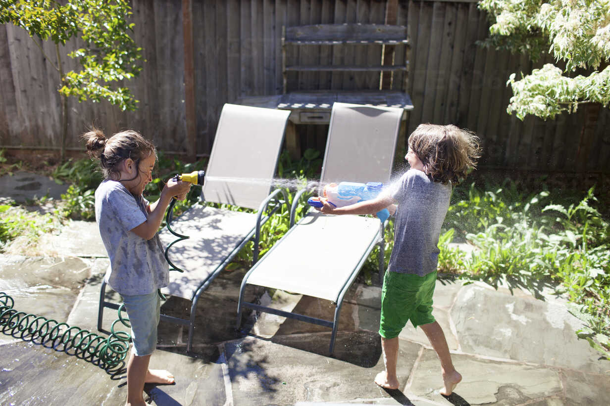 High angle view of playful brothers playing with water in yard during sunny day - CAVF13674 - Cavan Images/Westend61