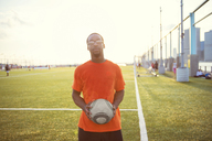 Portrait of sportsman with ball standing on soccer field - CAVF13692