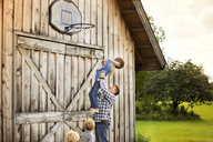 Happy father carrying daughter while playing basketball with children - CAVF13752