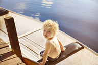 High angle view of boy sitting in boat on lake - CAVF13779