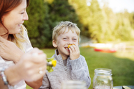 Son enjoying with mother on picnic table - CAVF13800
