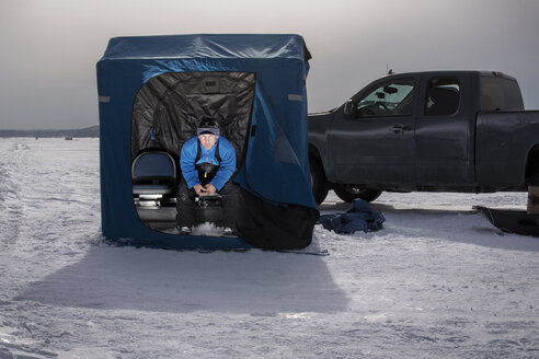 Man sitting in tent on frozen lake - CAVF13935