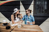 Young couple talking while sitting by table at sidewalk cafe - CAVF13950