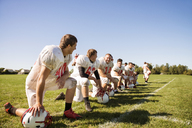 Happy football team kneeling on grassy field against sky - CAVF14001
