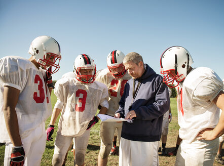 Coach explaining to American football players standing on field - CAVF14004