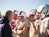 Coach discussing with American football players on sunny day - CAVF14007