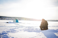 Man sitting on frozen lake against sky on sunny day - CAVF14070