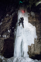 Low angle view of ice climber climbing on frozen waterfall - CAVF14145