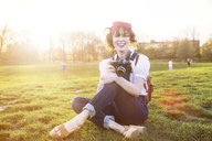Portrait of happy woman with camera sitting in park - CAVF14190