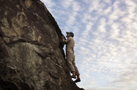 Low angle view of man rock climbing against sky - CAVF14214