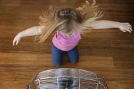 High angle view of girl with arms outstretched kneeling by electric fan on hardwood floor - CAVF14322