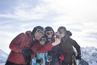 Family taking selfie with smart phone while standing at ski mountain - CAVF14463
