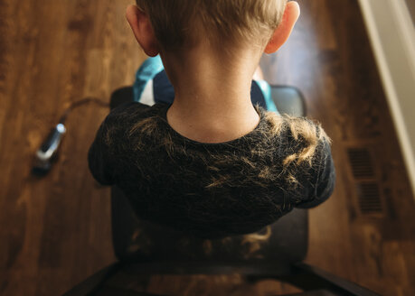 Rear view of boy sitting on barber chair - CAVF14499