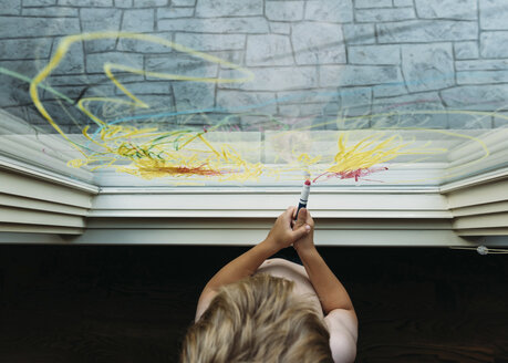Boy drawing with crayon on window at home - CAVF14502