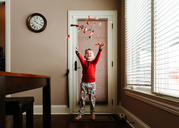 Happy boy throwing confetti while standing on doormat by door at home - CAVF14559