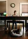Boy painting his fingers at table while Shih Tzu relaxing in pet bed - CAVF14562