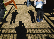 Shadow of sons swinging while father standing at playground - CAVF14580