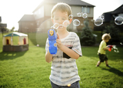 Brothers playing with bubble toy guns while standing in yard - CAVF14592