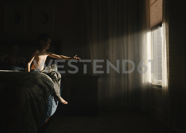 Shirtless boy trying to touch sunlight while sitting on bed in darkroom - CAVF14598