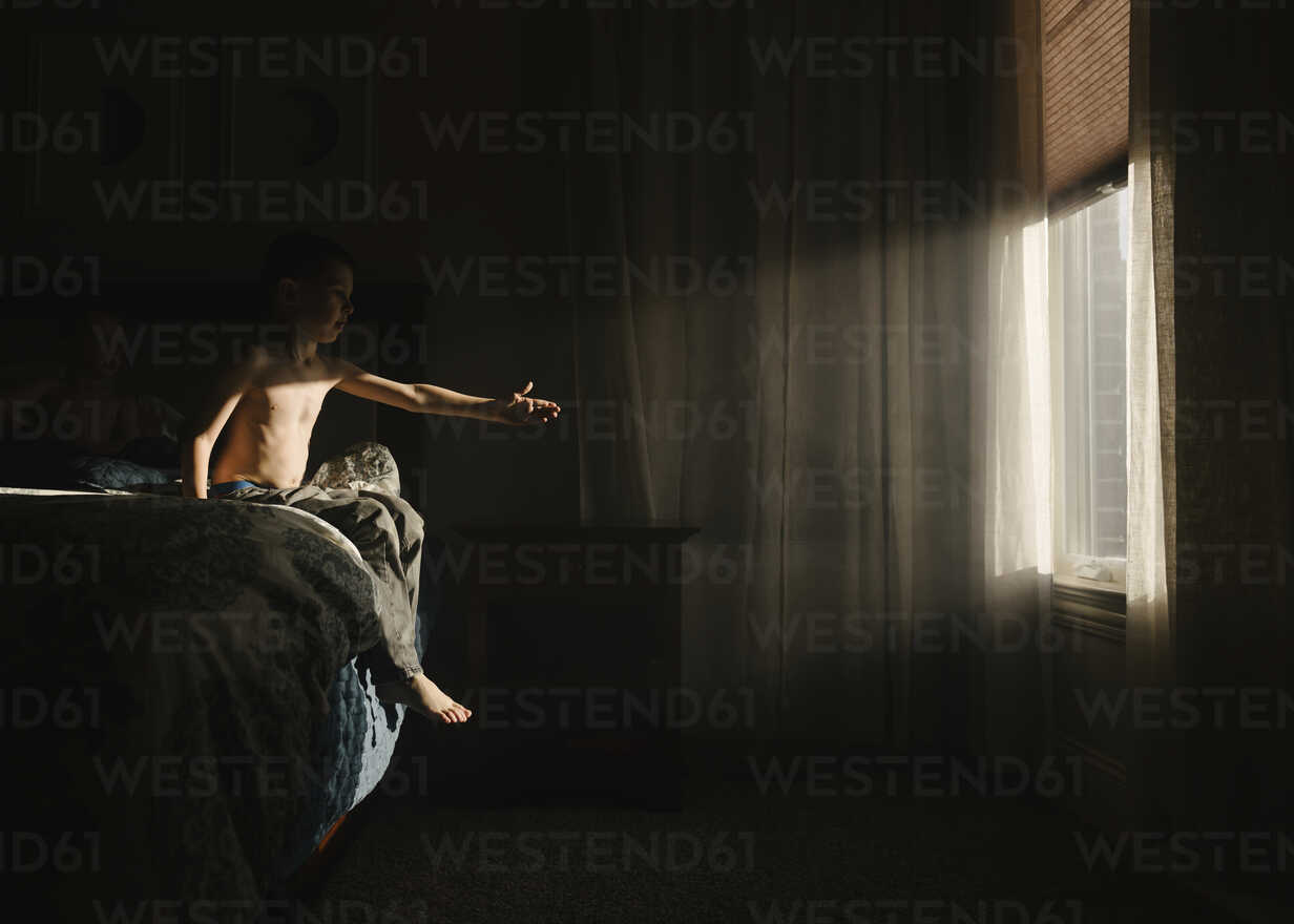 Shirtless boy trying to touch sunlight while sitting on bed in darkroom - CAVF14598 - Cavan Images/Westend61