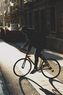 Man riding bicycle on footpath during sunset - CAVF14682