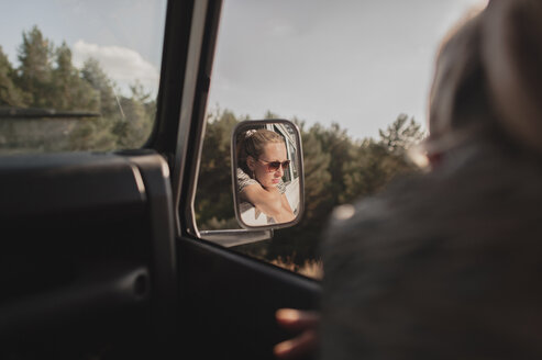 Reflection of woman seen in side-view mirror of car - CAVF14703