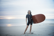 Full length portrait of confident female surfer carrying surfboard at Delray Beach - CAVF14727