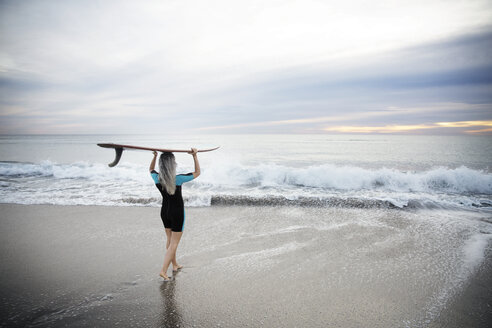 Rear view of female surfer carrying surfboard on head while walking towards sea on Delray beach - CAVF14733
