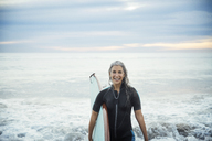 Portrait of happy wet female surfer carrying surfboard at Delray beach - CAVF14736