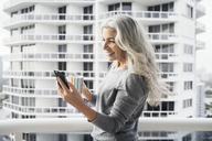 Happy mature woman using smart phone while holding coffee mug on balcony against building - CAVF14775