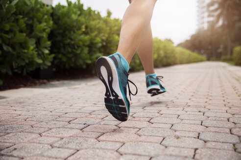 Low section of mature woman running on footpath - CAVF14799