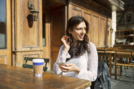 Thoughtful woman holding smart phone while sitting at sidewalk cafe - CAVF14808