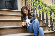 Happy woman holding disposable coffee cup while sitting on steps - CAVF14814