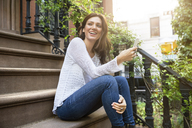 Happy woman holding smart phone while sitting on steps - CAVF14817