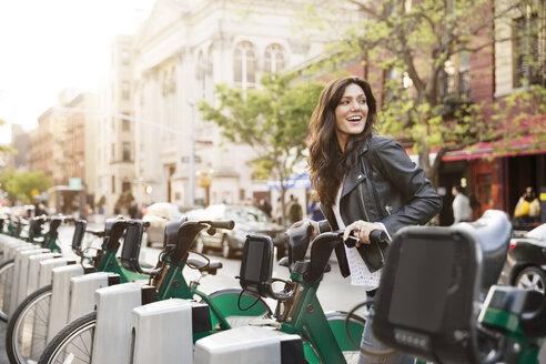 Happy woman unlocking bike share on street - CAVF14826