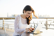 Happy woman using tablet computer at cafe on promenade during sunset - CAVF14835