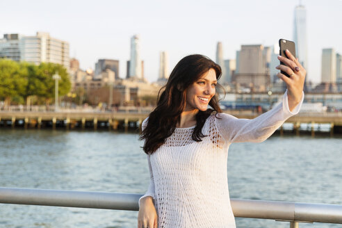 Happy woman taking selfie while standing on promenade with One World Trade Center in background - CAVF14838