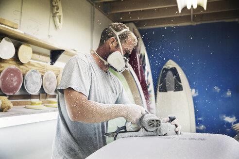 Man using plane on surfboard in workshop - CAVF14865