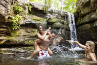 Cheerful friends laughing and splashing in river by waterfall - CAVF14874