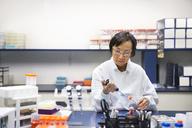 Senior female scientist using pipette in laboratory - CAVF14988
