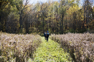 Rear view of hikers walking on field during autumn - CAVF15012