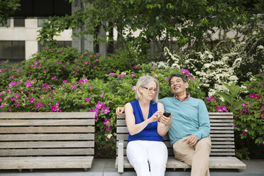 Happy mature couple using smart phone sitting on bench in park - CAVF15057
